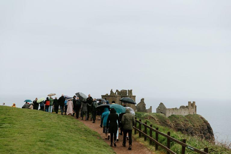 wedding guests approach Dunnottar Castle, Stonehaven