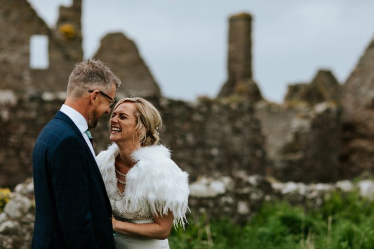 bride and groom laughing at Dunnottar Castle, Stonehaven