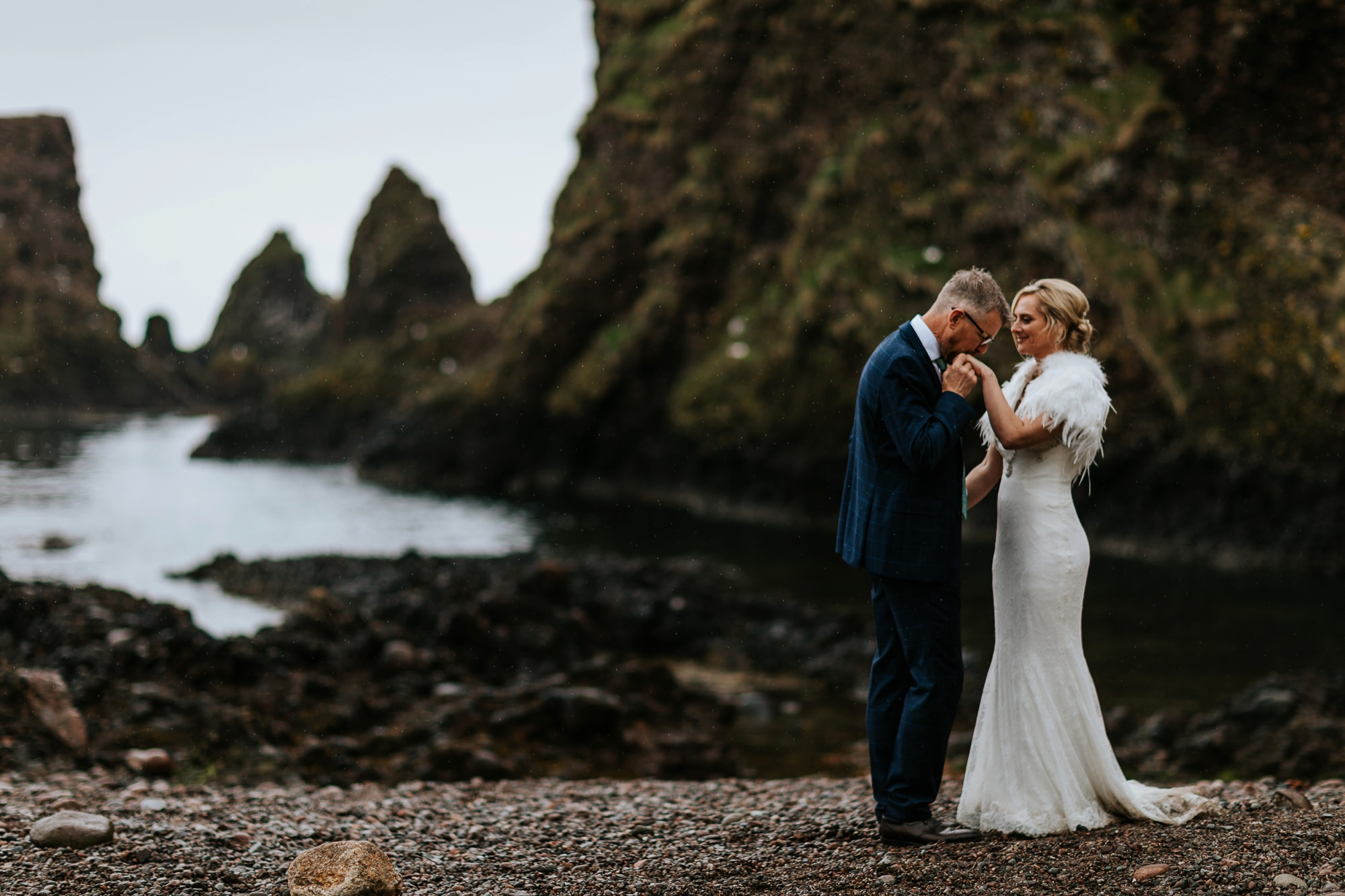 groom kissing bride's hand at beach at Dunnottar Castle, Stonehaven