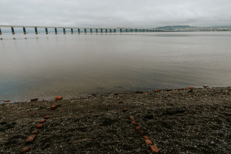 outline of wedding area on beach and Tay bridge